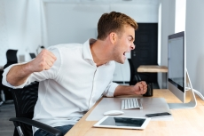 Aggressive furious businessman shouting and working with computer in office