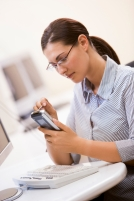 Woman in computer room using personal digital assistant
