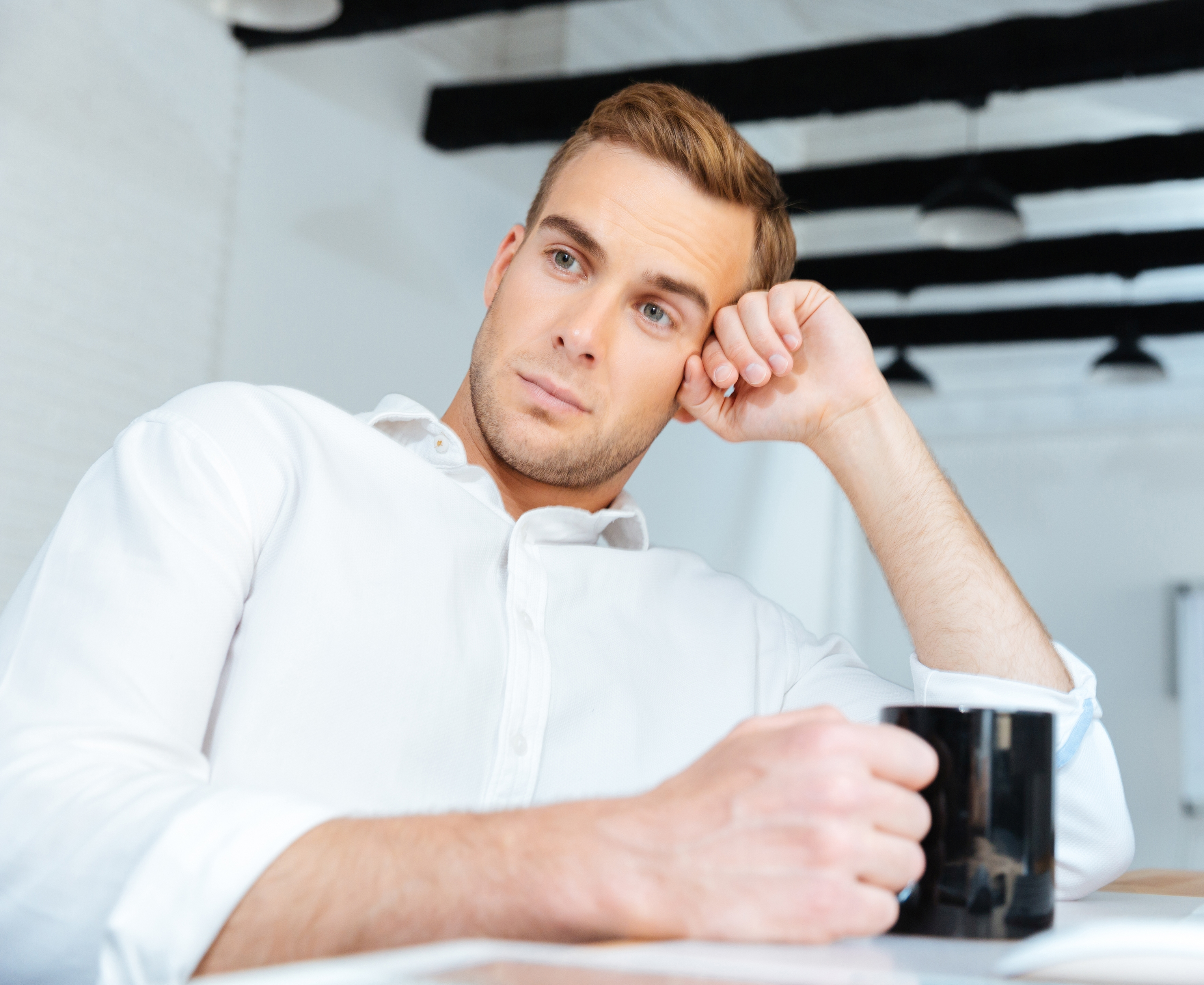 Thoughtful businessman drinking coffee and thinking at workplace